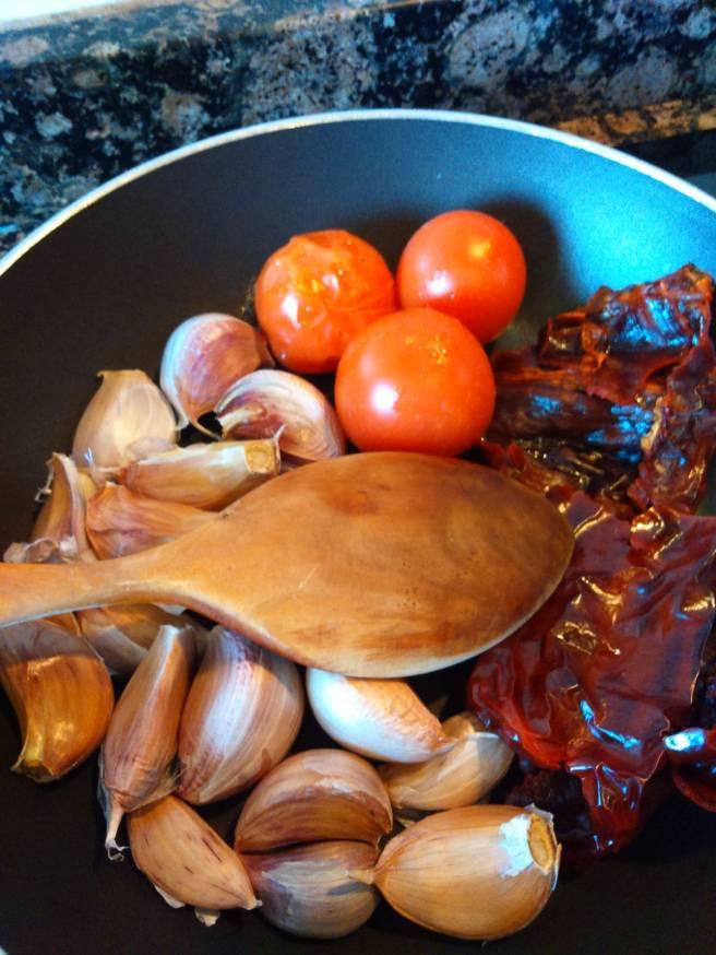 Els alls, les tomaquetes i el pebrot escalivant-se per al romesco
