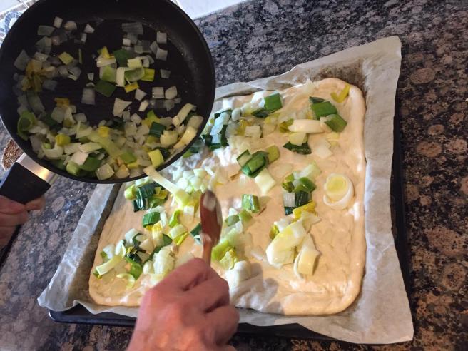 Posant la ceba i l'all porro ofegadets sobre la massa de pa fermentada