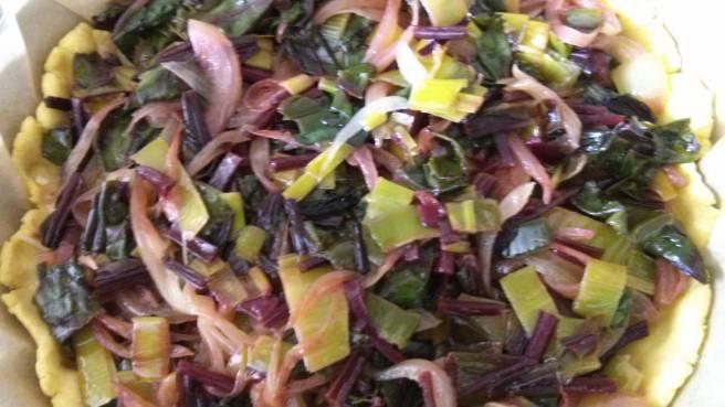Quiche de fulles de remolatxa, ceba i porro, hi afegim les verdures sobre la pasta trencada